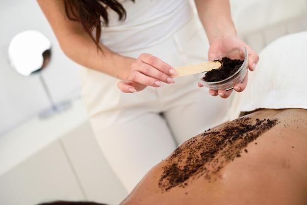 De vrouw maakt huid van het lichaam met koffiescrub schoon in kuuroordwellnesscentrum. Gratis Foto