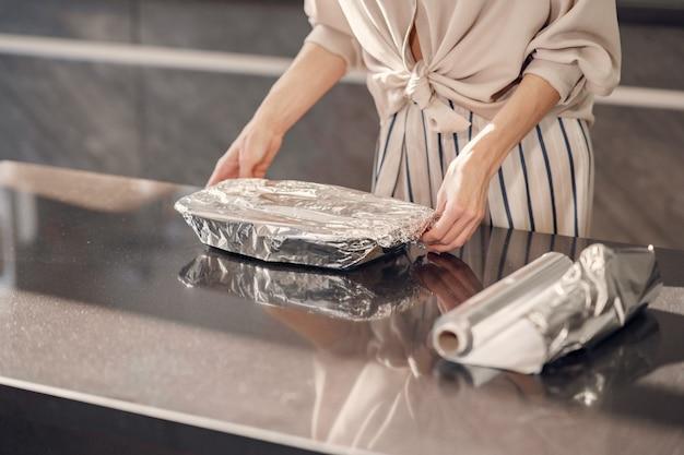 De vrouw maakt thuis een diner in de keuken Gratis Foto