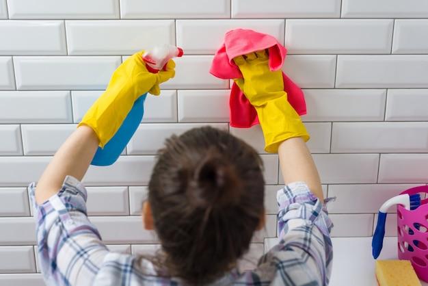 De vrouw maakt thuis in de badkamers schoon Premium Foto
