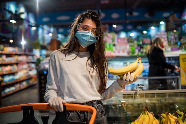 De vrouw met chirurgisch masker gaat bananen kopen Gratis Foto