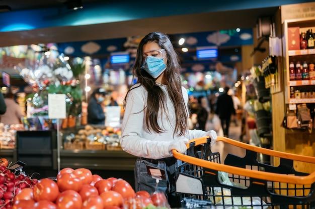 De vrouw met chirurgisch masker gaat tomaten kopen Gratis Foto