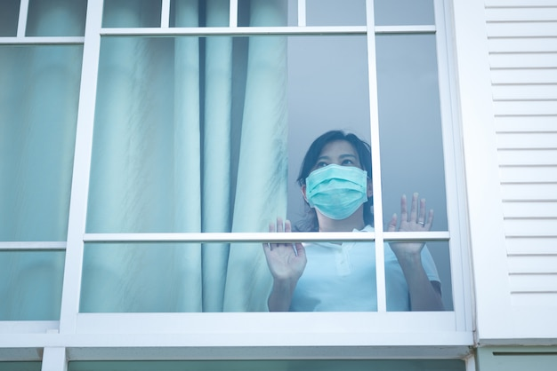 De vrouw met een medisch masker stond verdrietig naar het raam in huis te kijken voor zelfquarantaine Premium Foto