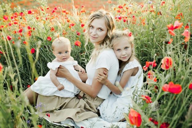 De vrouw met haar twee dochters buigt op papavergebied Gratis Foto
