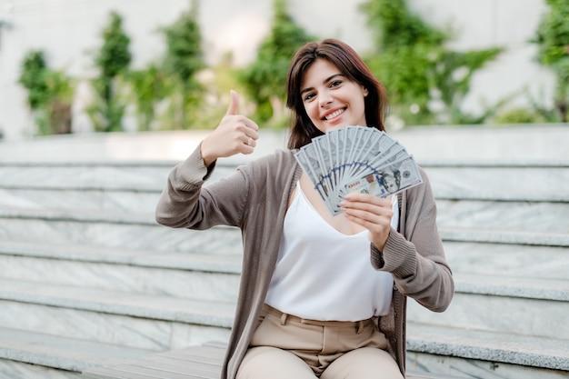 De vrouw met in hand dollargeld toont duimen Premium Foto
