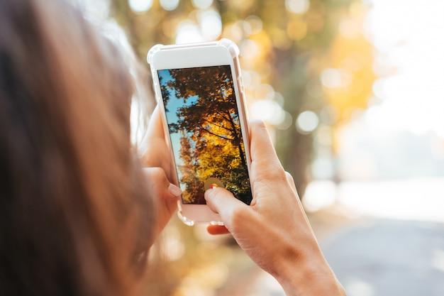 De vrouw neemt een foto van een de herfstboom op een straat Gratis Foto