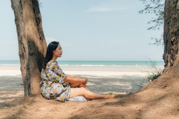 De vrouw ontspant op het strand onder de pijnboomboom in kalme atmosfeer. Premium Foto