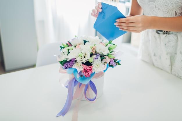 De vrouw opent envelop met kaart verlaten in boeket van bloemen in giftdoos op keuken. verrassing. aanwezig voor vakantie Premium Foto