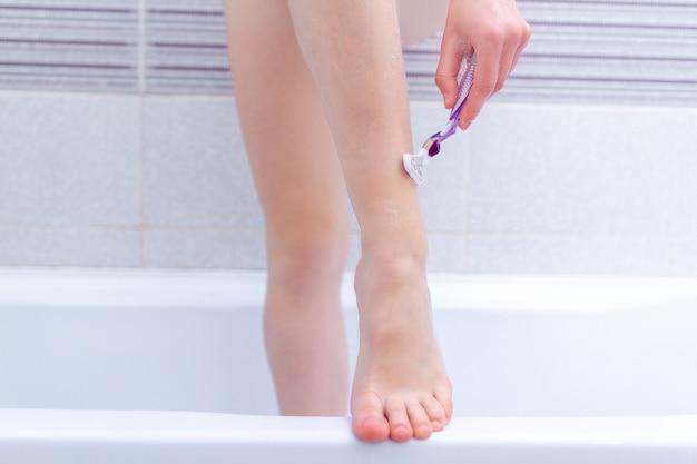 De vrouw scheert benen in de badkamers dicht omhoog gebruikend scheerapparaat. schoonheidsbehandelingen thuis. gladde huid Premium Foto