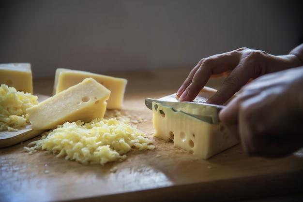 De vrouw sneed plakkaas voor kok die mes in de keuken met behulp van - mensen die voedsel met kaasconcept maken Gratis Foto