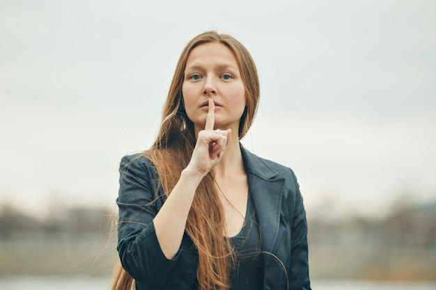 De vrouw toont een teken om rustig te spreken. het concept van manifestaties van emoties, problemen. Premium Foto