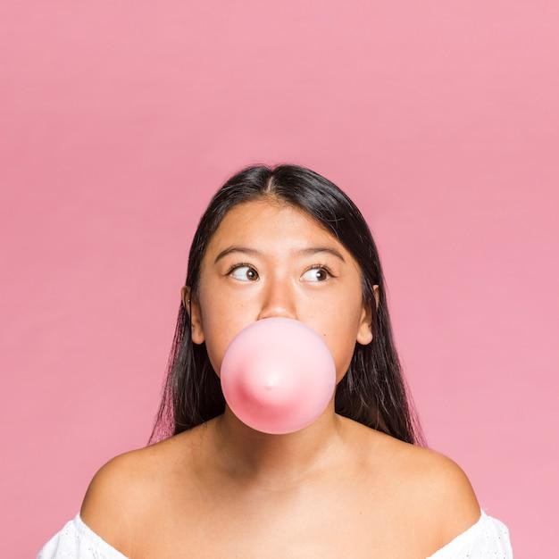 De vrouw van de close-up blaast een roze ballon op Gratis Foto