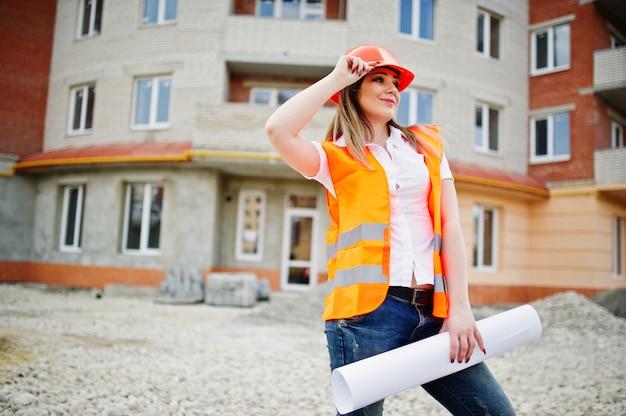 De vrouw van de ingenieursbouwer in eenvormig vest en oranje beschermend helm houdt handelspapier tegen de nieuwe bouw Premium Foto