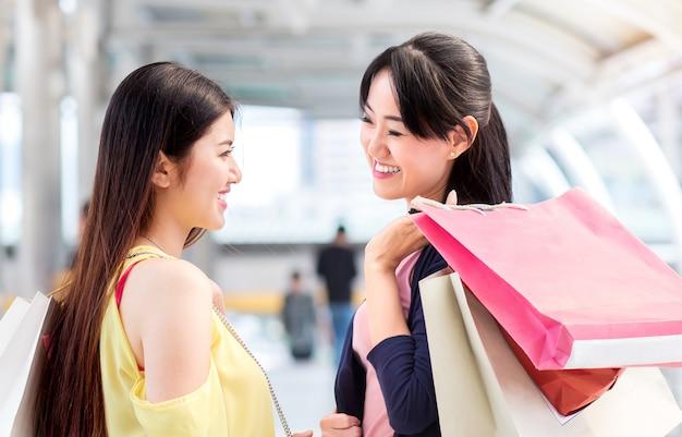 De vrouw van het gelukpaar, vriend, glimlach tijdens manier die samen dichtbij het winkelen van de maniermanier het winkelen opslag winkelen. Premium Foto