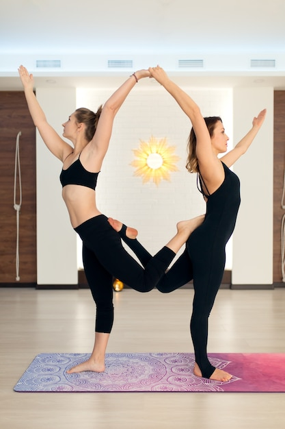 De vrouw van het paar in gymnastiek doet yoga uitrekkende oefeningen. fit en wellness levensstijl. Premium Foto