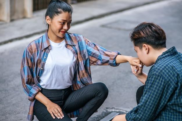 De vrouw van twee geliefden zat en kuste elkaar de hand. Gratis Foto