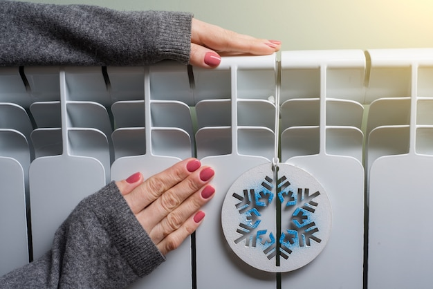 De vrouw verwarmt haar handen op het radiatorpaneel Premium Foto