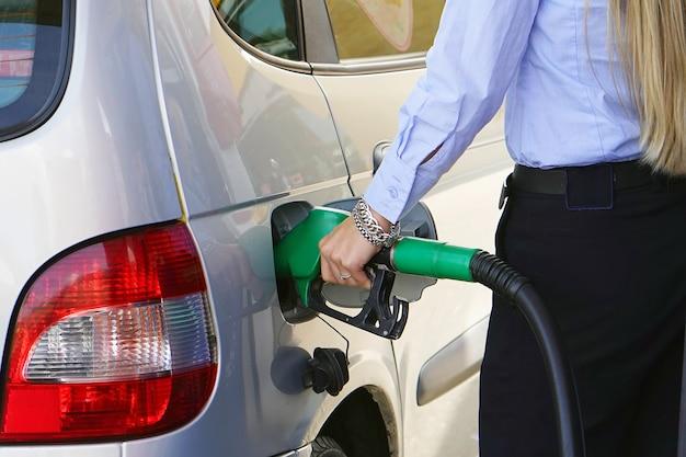 De vrouw vult benzine in haar auto bij een benzinestationclose-up. vrouwenhand die een brandstofpomp houden bij een post. Premium Foto