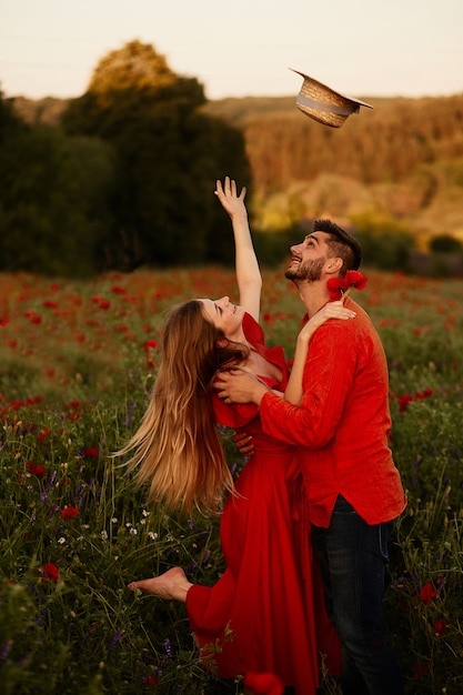 De vrouw werpt op haar hooihoed die zich met haar man op een groen gebied bevindt Gratis Foto