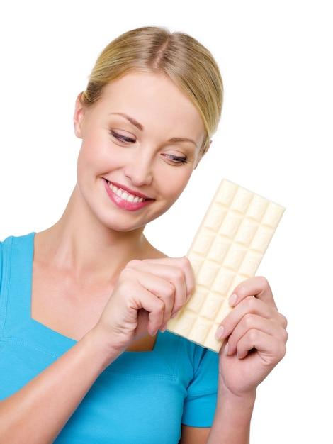 De vrouw wil een tegel zoete witte chocolade eten Gratis Foto