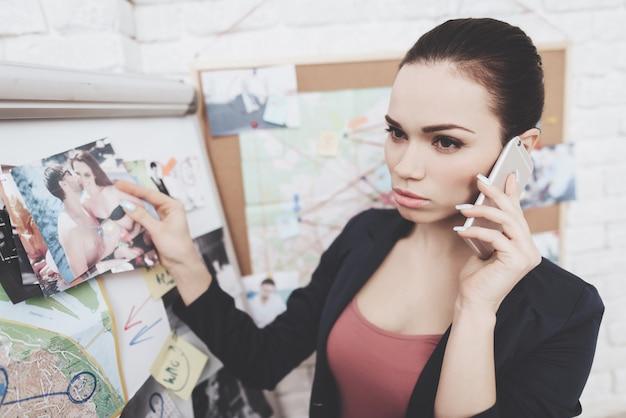 De vrouw zet foto's op aanwijzingskaart in bureau. Premium Foto