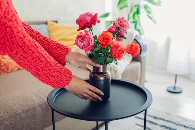 De vrouw zet vaas met bloemenrozen op lijst, huisvrouw die gezelligheid in flat behandelen Premium Foto