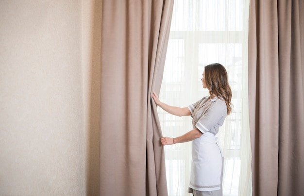 De vrouwelijke arbeider van het huishoudenkamma met het openen van gordijnen van venster in ruimte Gratis Foto