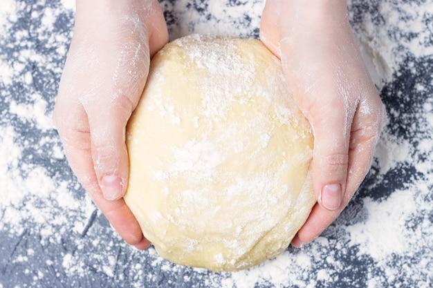 De vrouwelijke handen houden een rond deeg op grijze achtergrond, hoogste mening. Premium Foto
