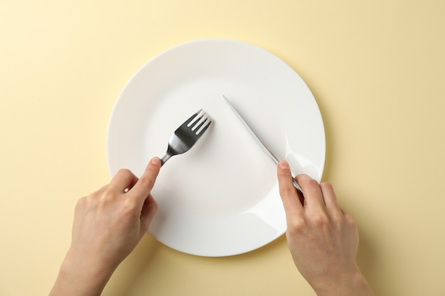 De vrouwelijke handen houden vork en mes op beige achtergrond met plaat, hoogste mening Premium Foto