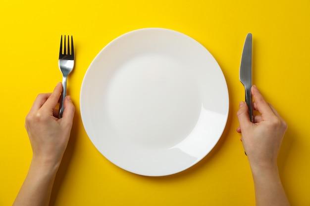 De vrouwelijke handen houden vork en mes op gele achtergrond met plaat, hoogste mening Premium Foto