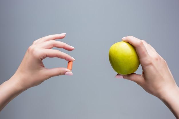 De vrouwelijke handen met appel en pillen op grijze achtergrond Gratis Foto