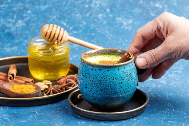 De vrouwelijke kop van de handholding van traditionele ayurvedische drank gouden kurkumamelk en plaat met zijn ingrediënten op blauw. Premium Foto