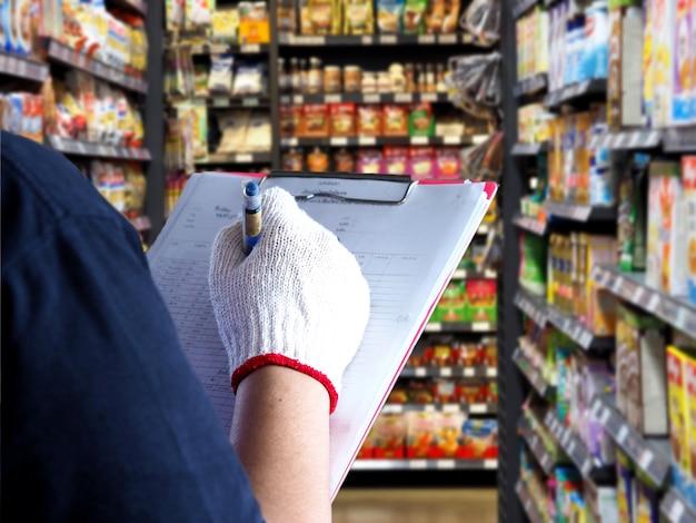 De vrouwelijke producten van de werknemerscontrole op de planken in de supermarkt. Premium Foto