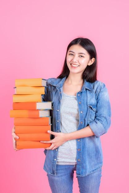 De vrouwelijke stapel van de tienerholding van boek op roze Gratis Foto