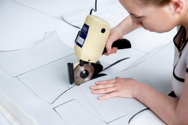 De vrouwelijke werknemer gebruikt elektrische scherpe stoffenmachine. fabricage van de textielindustrie Premium Foto