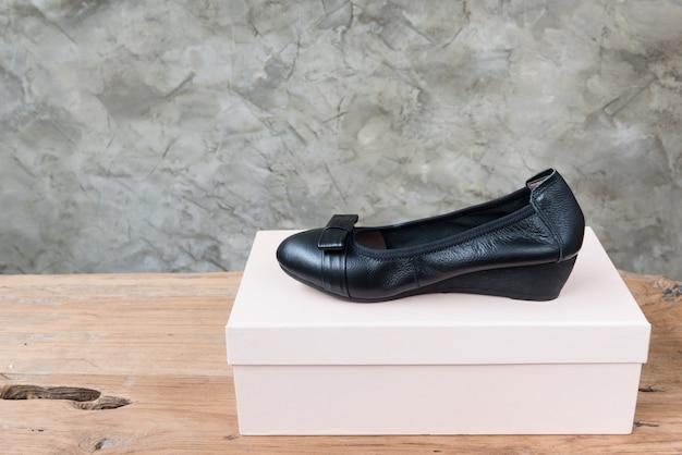 De vrouwelijke zwarte schoenen tonen op antieke houten lijst Premium Foto