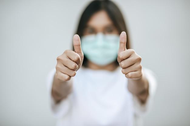 De vrouwen dragen maskers en markeren ze met hun duimen omhoog. Gratis Foto
