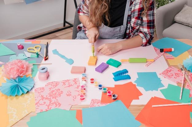 De vrouwenhand die van de kunstenaar kleurrijke klei snijdt die kleisnijder op lijst gebruikt Gratis Foto
