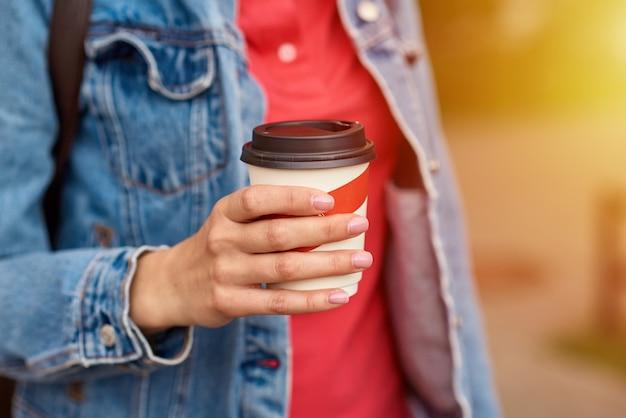 De vrouwenhand met document kop van koffie haalt in een stadsstraat weg Premium Foto