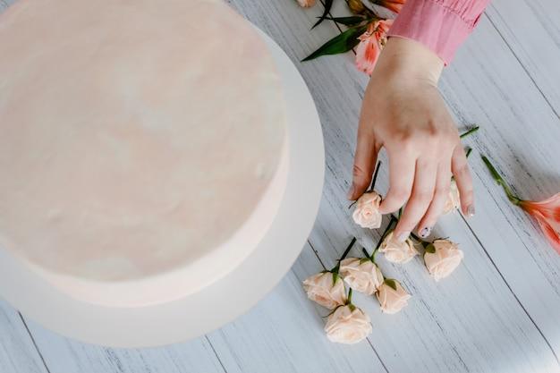 De vrouwenhand verfraait de roze cake van de huwelijksverjaardag met verse bloemen. Premium Foto
