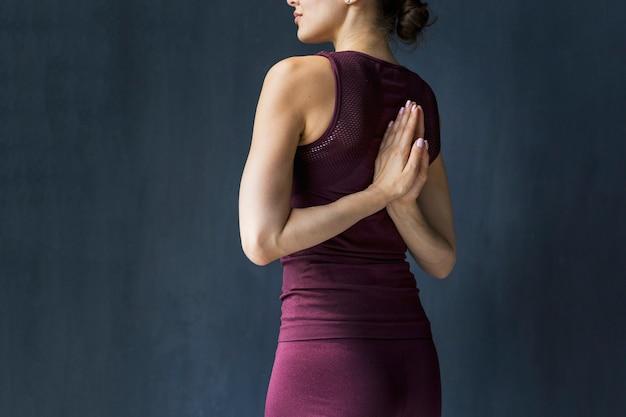De vrouwenholding dient terug het bidden positie achter haar in Gratis Foto