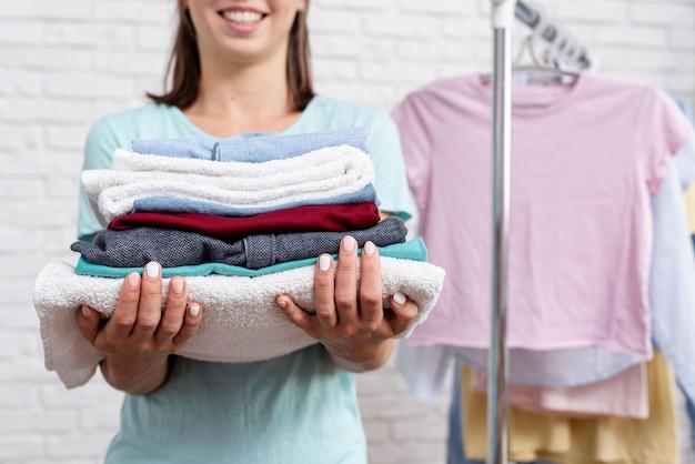 De vrouwenholding van de close-up gevouwen kleren en handdoeken Gratis Foto