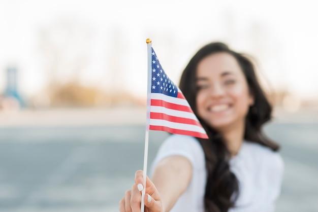 De vrouwenholding van de close-upvlag van de vs het glimlachen Gratis Foto