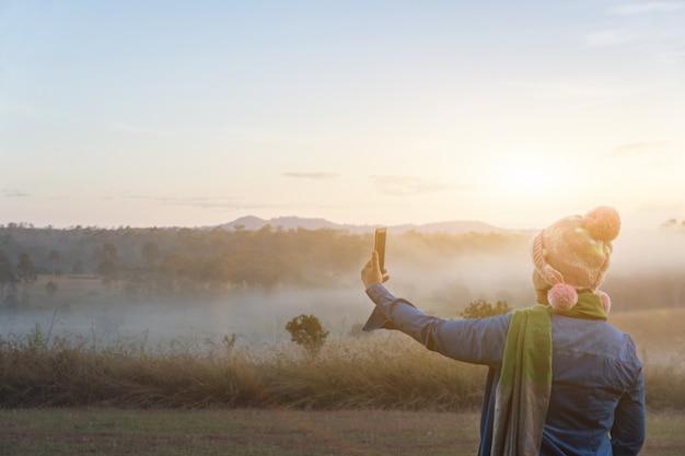 De vrouwentoeristen nemen een foto met smartphone tijdens dramatische zonsopgang bij de mistige de zomerochtend, concept openlucht het kamperen avontuur Premium Foto