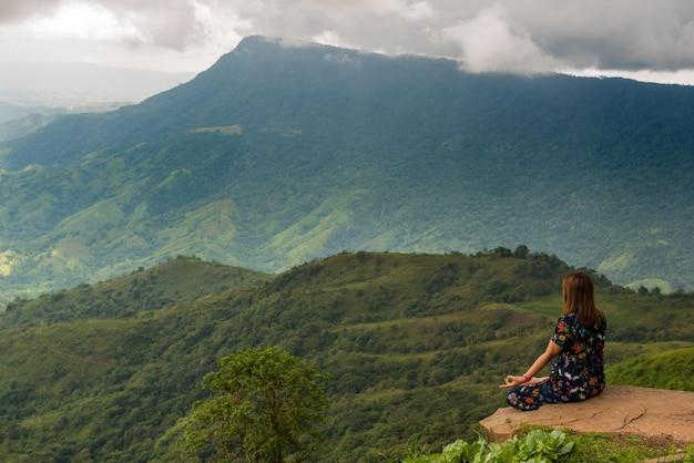 De vrouwenzitting die van de yoga meditatie op de rots met bergachtergrond doet. Premium Foto