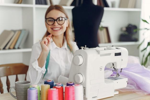 De vrouwenzitting in studio en naait doek Gratis Foto