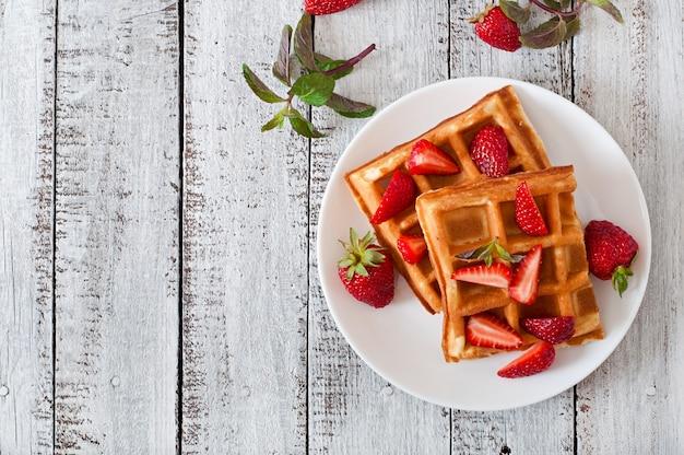 De wafels van belgië met aardbeien en munt op witte plaat Gratis Foto
