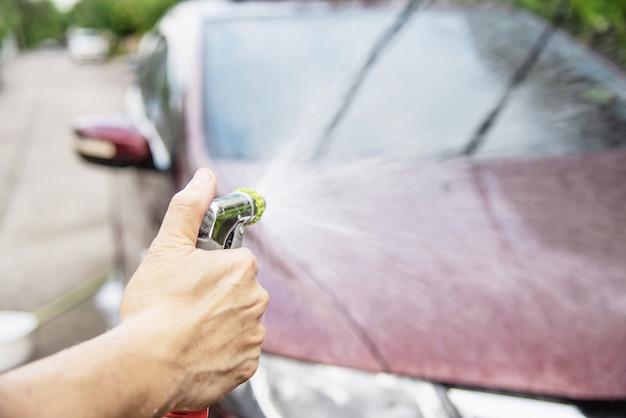 De wasauto van de mens die shampoo en water gebruikt Gratis Foto