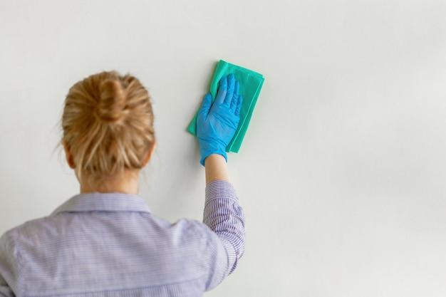 De werknemer dient blauwe rubber beschermende handschoen afvegende muur van stof met droge vod in. Premium Foto