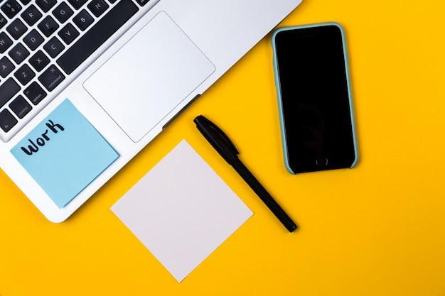 De werkruimte van het huisbureau met laptop en document sticker op gele achtergrond. geld, grafiek, grafiek huis plat lag, bovenaanzicht werk bedrijfsconcept. werk thuis concept op de quarantaine van het coronavirus Premium Foto