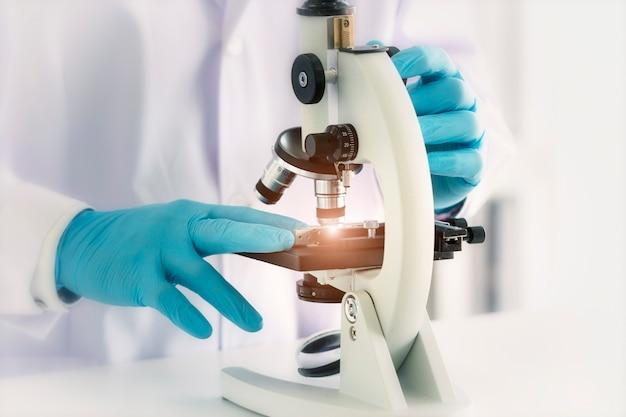 De wetenschapper gebruikt een microscoop in een analytisch laboratorium. Premium Foto